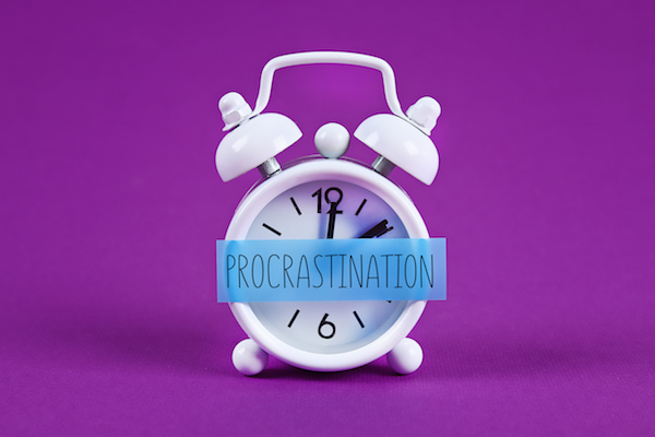 Clock on. purple background with procrastination written across it